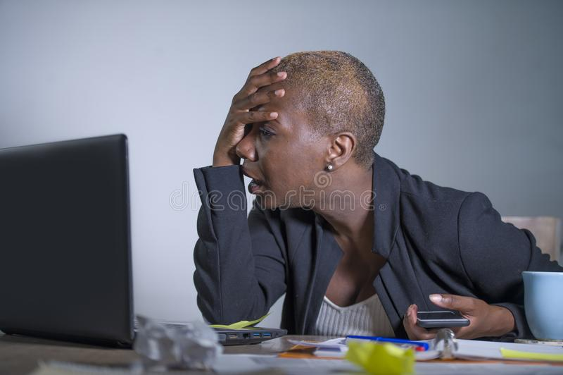 Young desperate and stressed african american business woman working at laptop computer desk at office suffering stress problem us. Ing mobile phone overwhelmed royalty free stock images