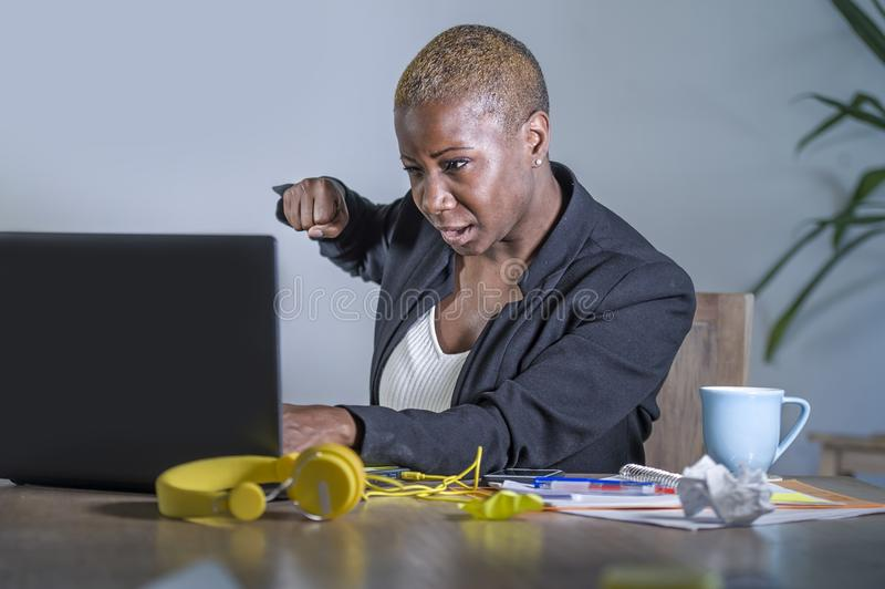 Young desperate and stressed african american business woman working at office desk suffering stress feeling overwhelmed punching stock photos