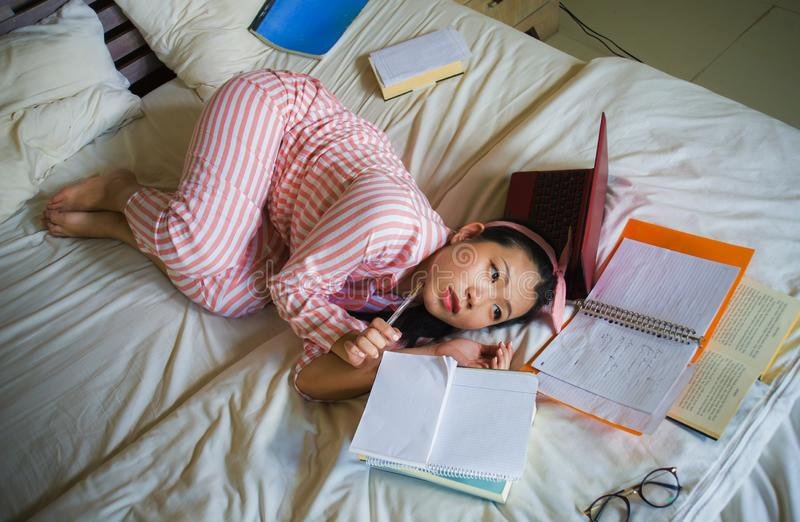 Young desperate and tired Asian Korean university student girl feeling overwhelmed and stressed preparing exam studying with stock photo