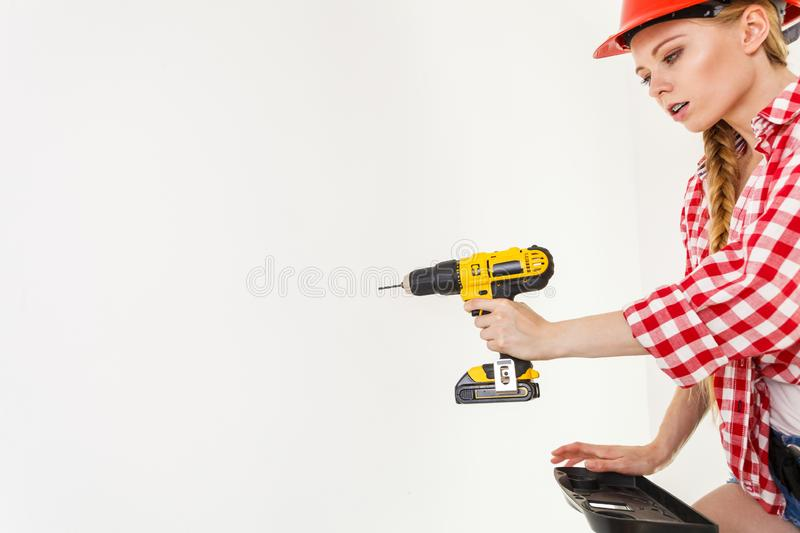 Woman using drill on ladder royalty free stock photo