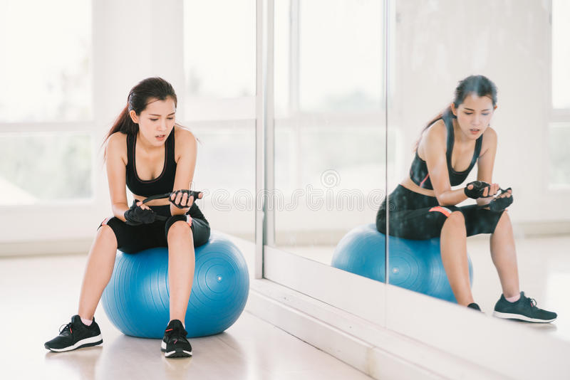 Young and determined Asian girl on fitness ball at gym with mirror, sport and healthy lifestyle concept royalty free stock photography