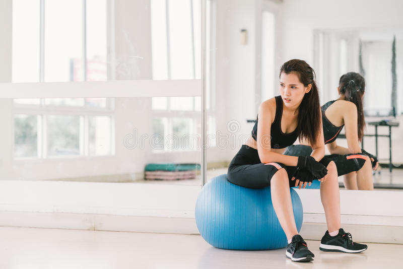 Young and determined Asian girl on fitness ball at gym with copy space, sport and healthy lifestyle concept.  royalty free stock images