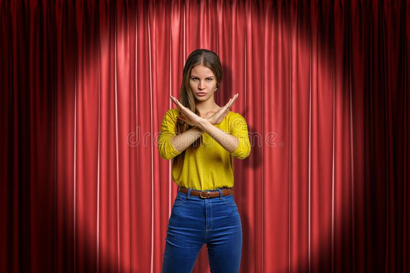 Young determined woman wearing jeans and yellow shirt making rejection gesture on red stage curtains background royalty free stock photo