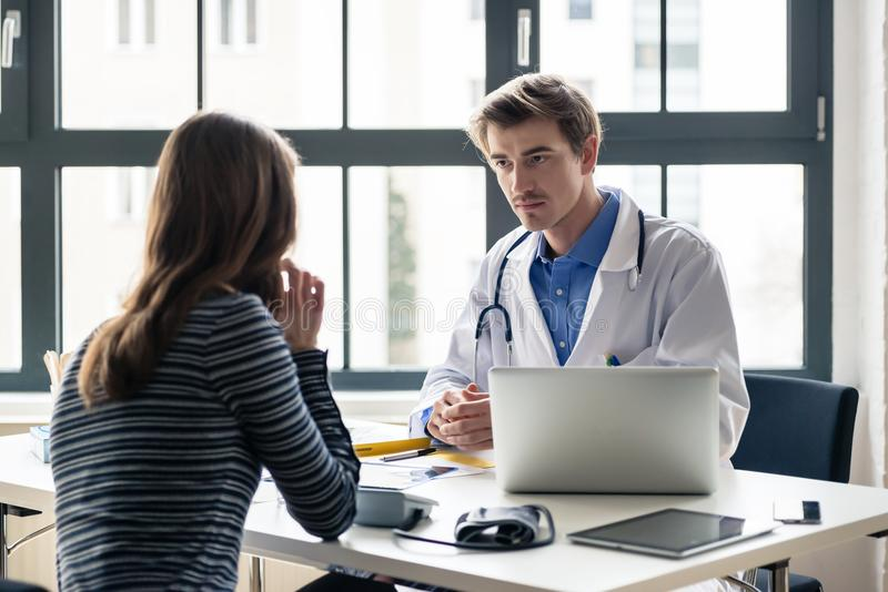 Young devoted doctor listening with attention to his patient royalty free stock photos