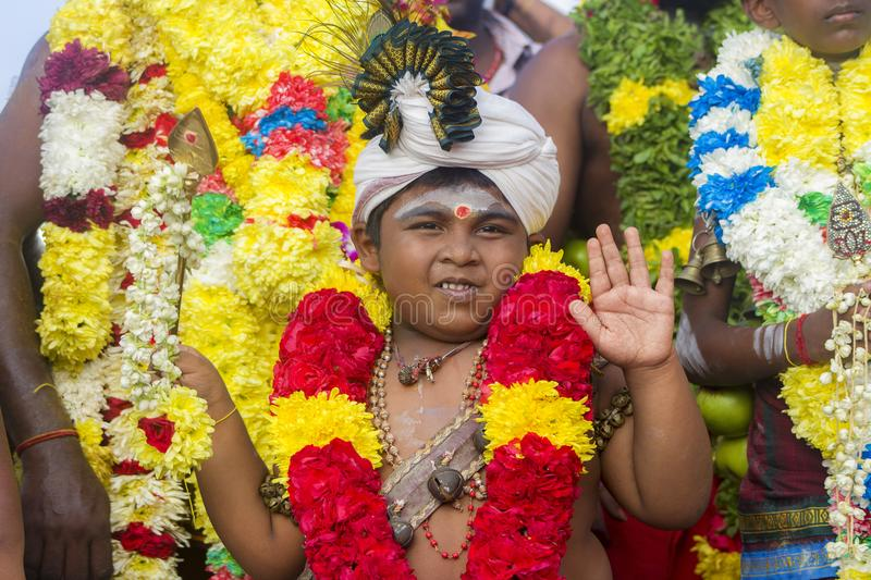 Young boy devotee at Thaipusam festival with flowers royalty free stock image