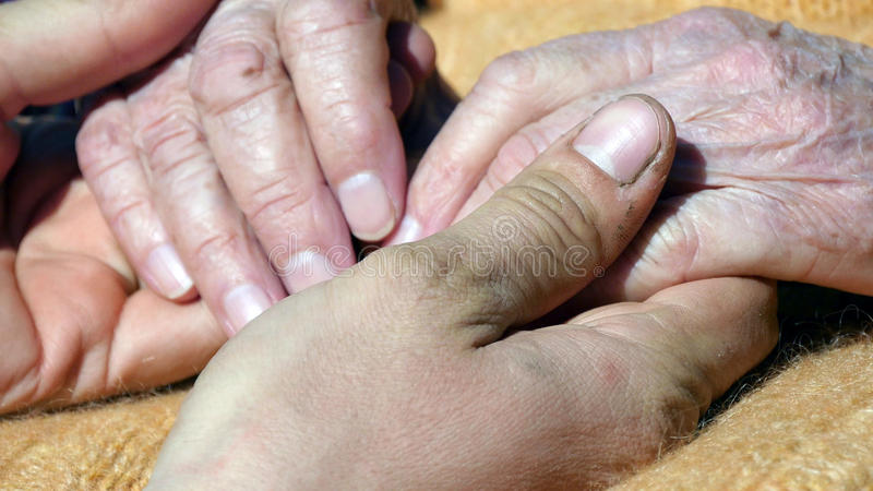 A young dirty working man`s hands comforting an elderly pair of hands of grandmother outdoor royalty free stock photography