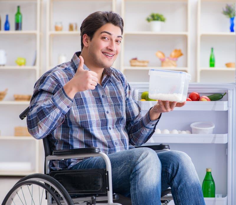Young disabled injured man opening the fridge door royalty free stock photos