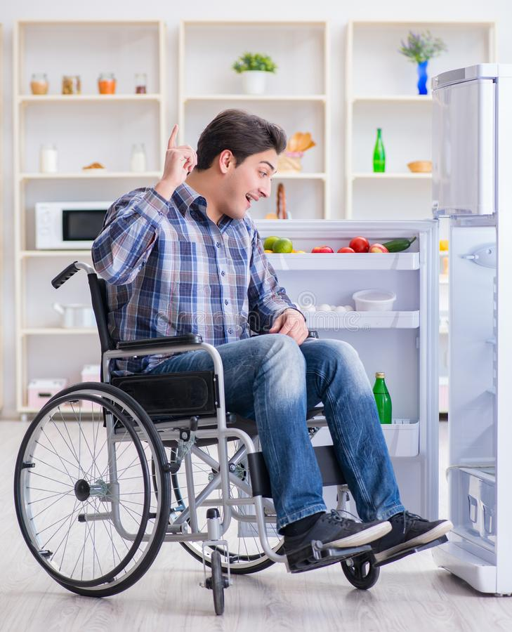 Young disabled injured man opening the fridge door stock photography
