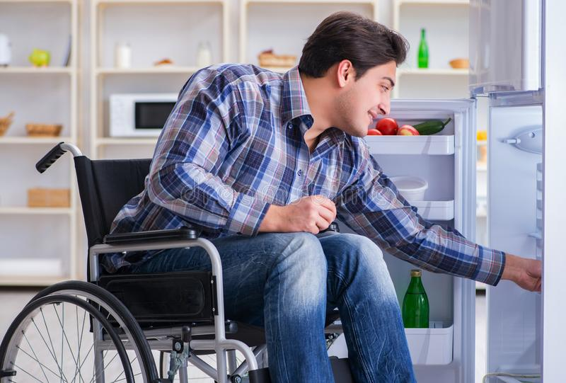 Young disabled injured man opening the fridge door royalty free stock images