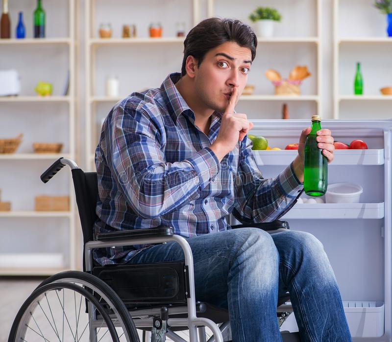 Young disabled injured man opening the fridge door. The young disabled injured man opening the fridge door royalty free stock photography