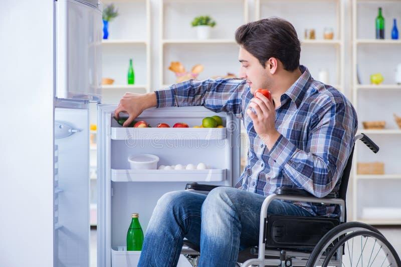 The young disabled injured man opening the fridge door stock photos
