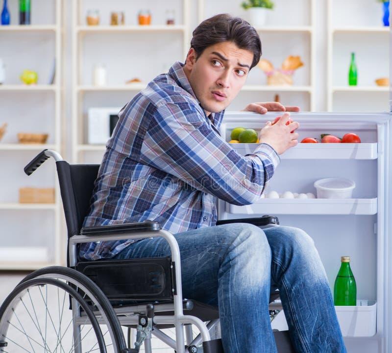 Young disabled injured man opening the fridge door stock photos
