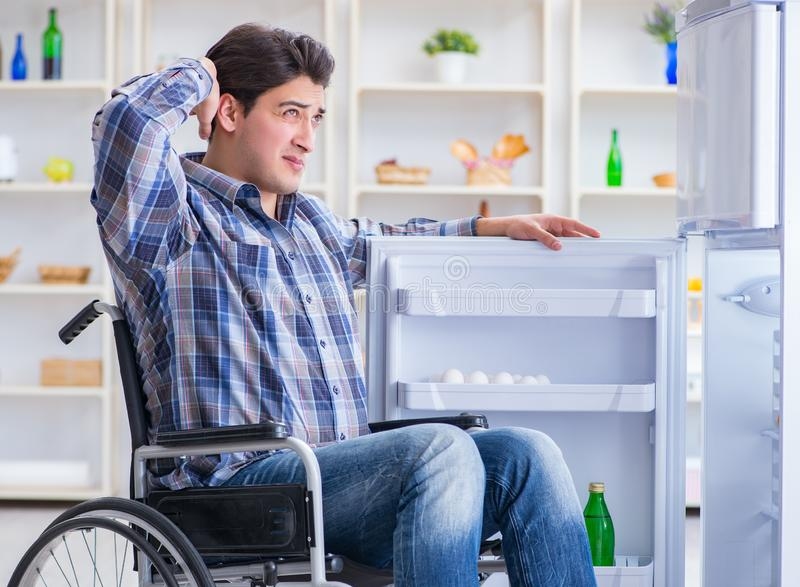 Young disabled injured man opening the fridge door royalty free stock photos