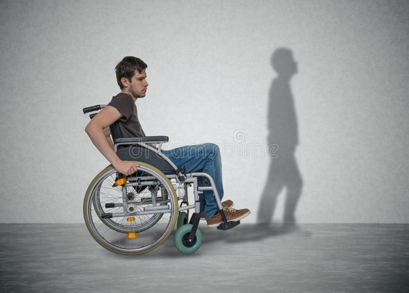 Young disabled man on wheelchair has hope for recovery. His shadow is walking near.  stock photos