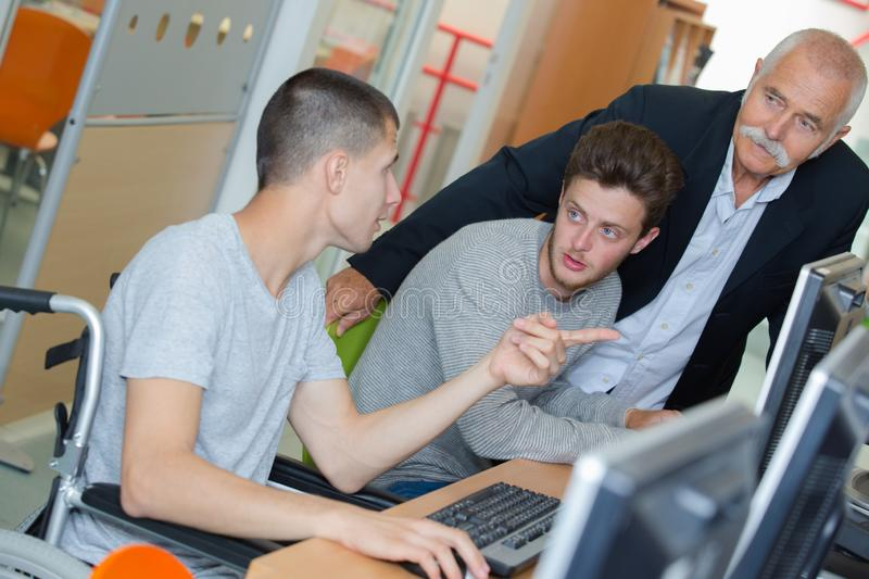 Young disabled man studying with friend and teacher. Young disabled men studying with friend and teacher student stock images