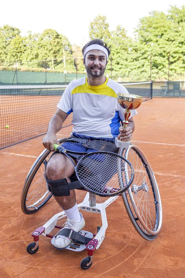Young disabled tennis player shows the cup royalty free stock image