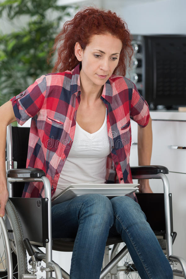 Young disabled woman struggling to move in house stock photo