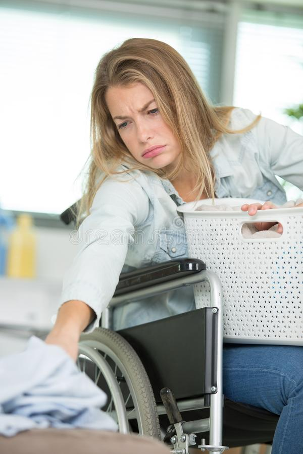 Young disabled woman on wheelchair using washing machine stock photography