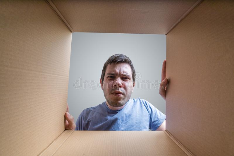 Young disappointed man is looking on gift inside cardboard box stock images