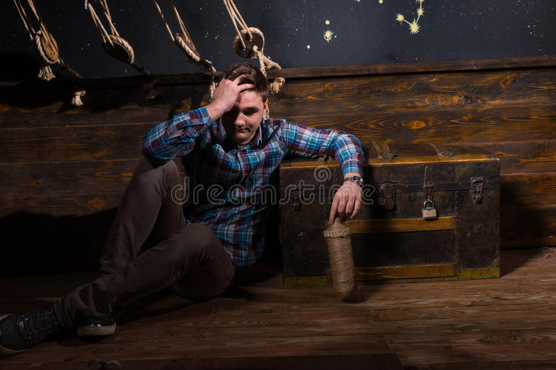 A young disappointed man sits near a chest, holding glass bottle royalty free stock photo