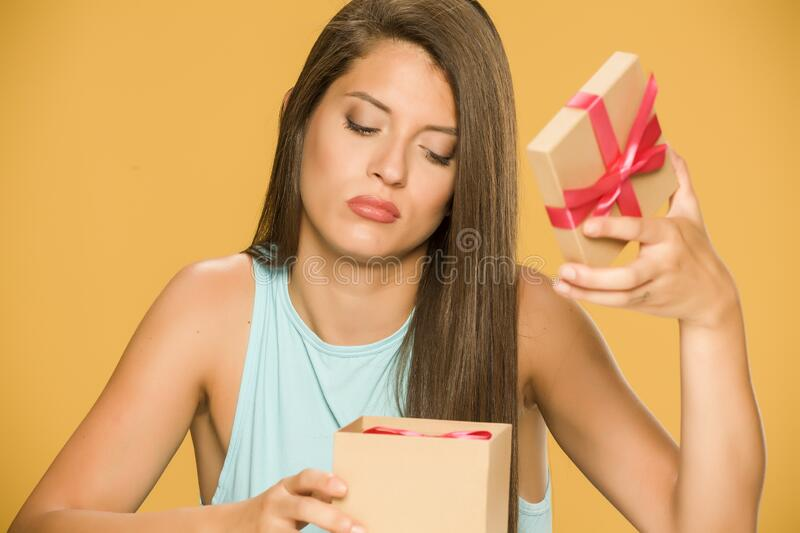 Young disappointed woman opening a present box stock images