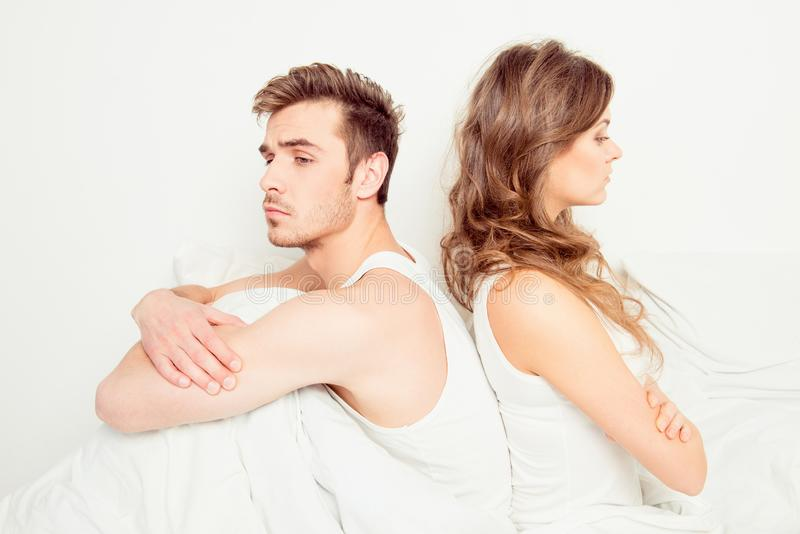 Young disconnected couple with problems sitting on the bed.  royalty free stock photography
