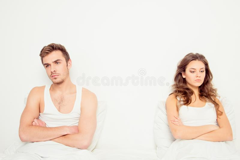 Young disconnected couple sitting on the bed.  royalty free stock photography