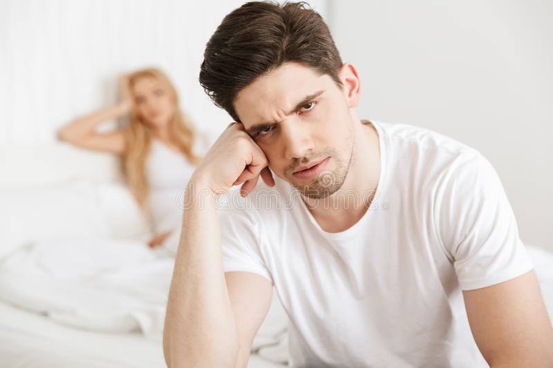 Young displeased loving couple in bed stock photography