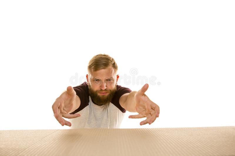 Young man opening the biggest postal package isolated on white. Young dissapointed man opening the biggest postal package isolated on white. Shocked male model royalty free stock photos