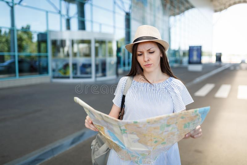 Young dissatisfied traveler tourist woman holding paper map, standing at international airport. Female passenger. Traveling abroad to travel on weekends getaway stock image