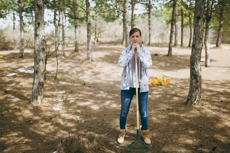 Young dissatisfied woman in casual clothes cleaning using rake for garbage collection in littered park. Problem of stock image