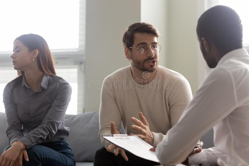 Young dissatisfied woman getting bored while husband talking with psychologist. Young dissatisfied women getting bored while husband discussing family problems royalty free stock image