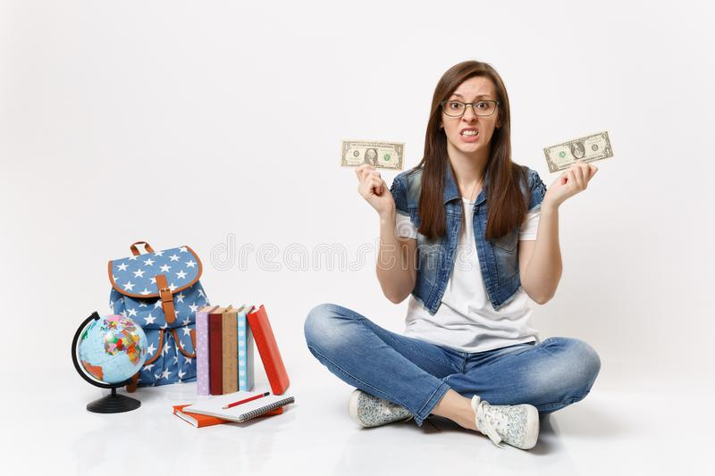 Young dissatisfied woman student hold dollar bills cash money feeling stressed by lack of money sit near globe backpack. Books isolated on white background royalty free stock images