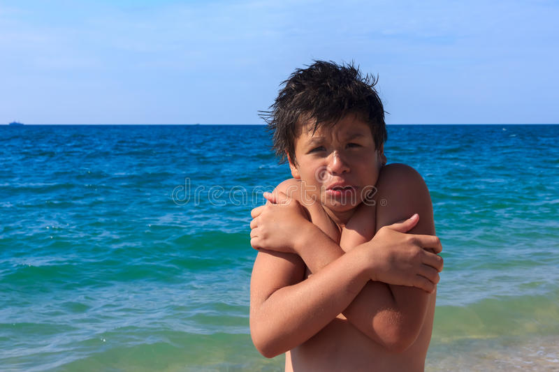 Young diver boy freezes on the sea beach stock photo