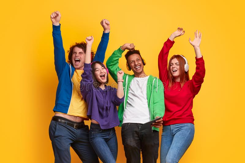 Young diverse friends listening to music and dancing. Excited multiracial young people in colorful outfits and headphones listening to music and dancing together royalty free stock photos