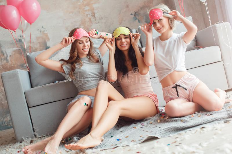 Slumber Party. Young women in sleeping mask together at home sitting on floor looking camera happy. Young diverse women wearing sleeping mask having slumber stock photos
