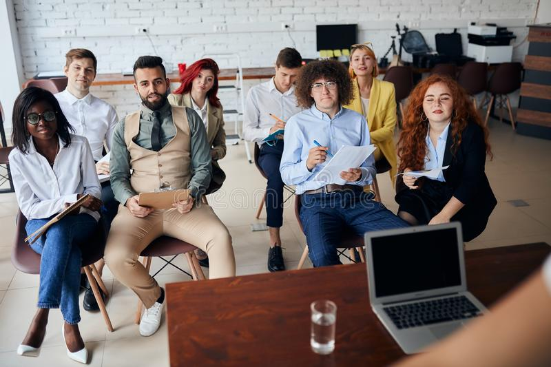 Young diversity team of employees listening to business coach on training in office royalty free stock photography