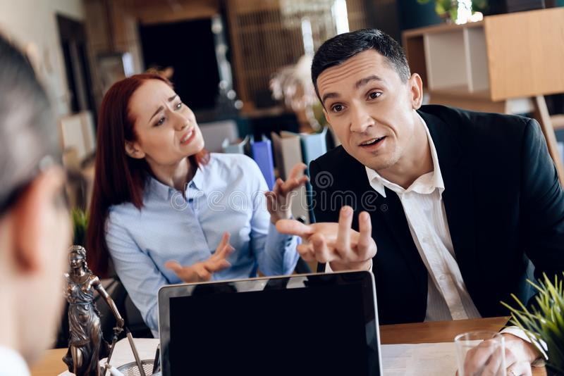 Young divorcing couple emotionally communicate in divorce lawyer office. stock photography