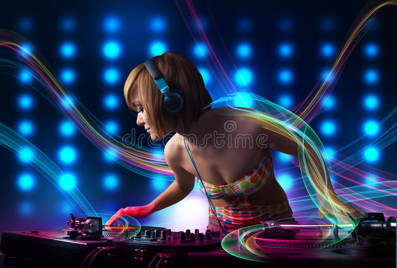 Young Dj girl mixing records with colorful lights. Beautiful young Dj girl mixing records with colorful lights royalty free stock photography