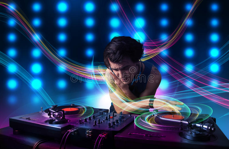 Young Dj mixing records with colorful lights. Attractive young Dj mixing records with colorful lights royalty free stock photos