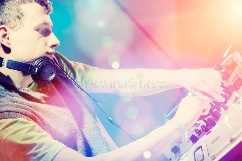 Young DJ playing records at a party in a nightclub. royalty free stock photo