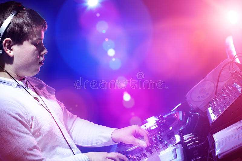 Young DJ playing records at a party in a nightclub. royalty free stock photos
