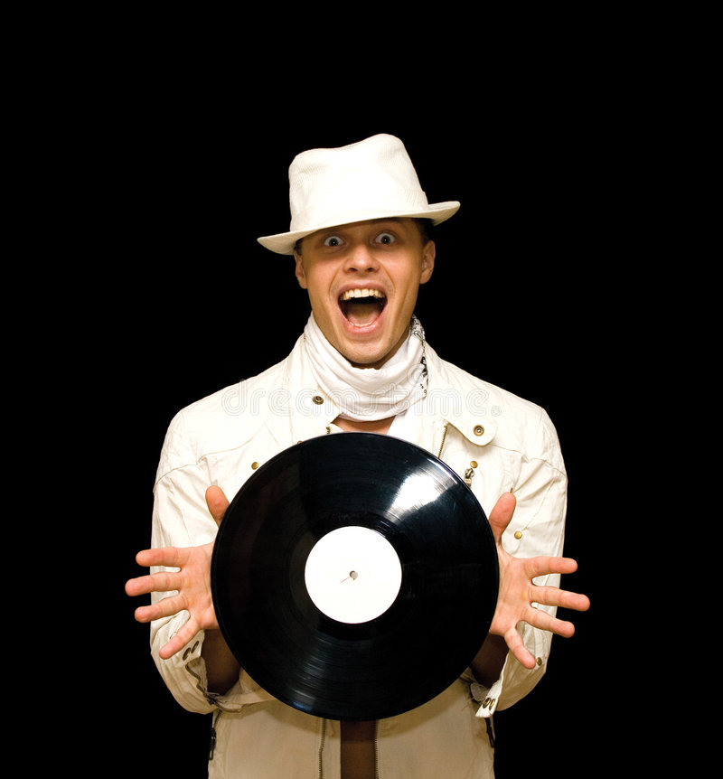 Young DJ in white costume holding vinyl record in. Portrait of handsome young DJ in white costume holding vinyl record in his hands royalty free stock photography