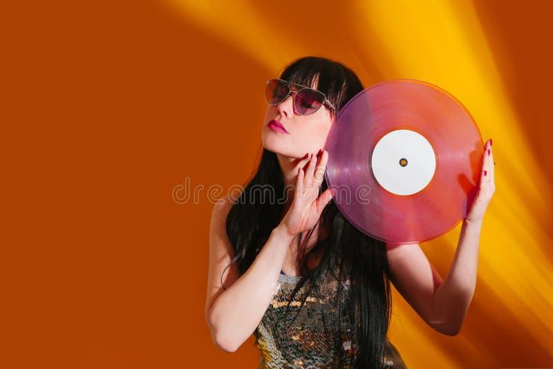 Dj disco girl party retro vintage yellow orange young woman vinyl glamour light sun sunlight set sunrise summer morning. Young DJ woman with pink vinyl enjoys royalty free stock photography