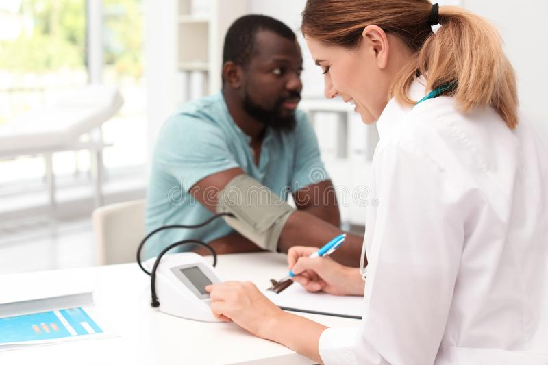 Young doctor checking African-American patient`s royalty free stock photography