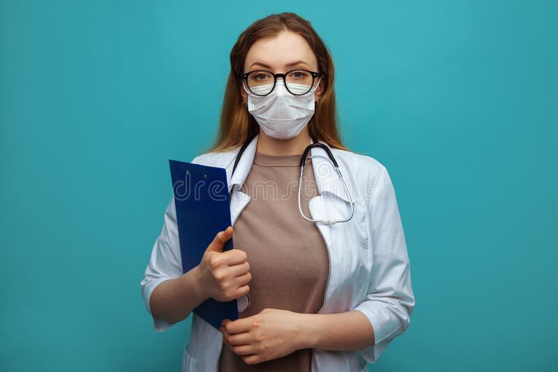 Young doctor with clipboard on blue background. Space for text.  stock images