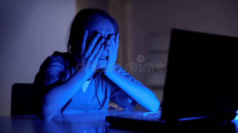 Young doctor crying working on laptop, stress from loss of patient, night shift stock images