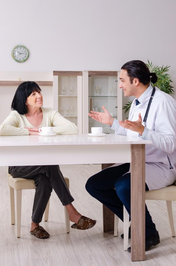 Young doctor examining senior old woman stock photo