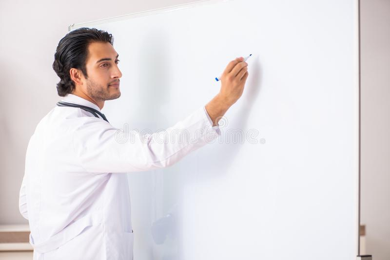 The young doctor in front of whiteboard royalty free stock image
