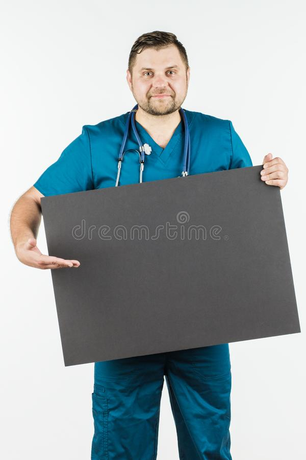 Young doctor holding a blank banner in the hands of copy space f stock photo
